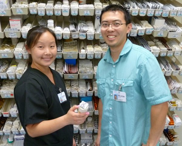 Pharmacy personnel in front of medication shelves.